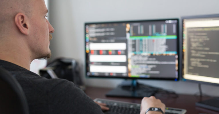 Mies ohjelmoi tietokoneen ääressä
