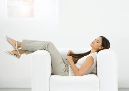Nainen lepää sohvalla valkoisessa huoneessa