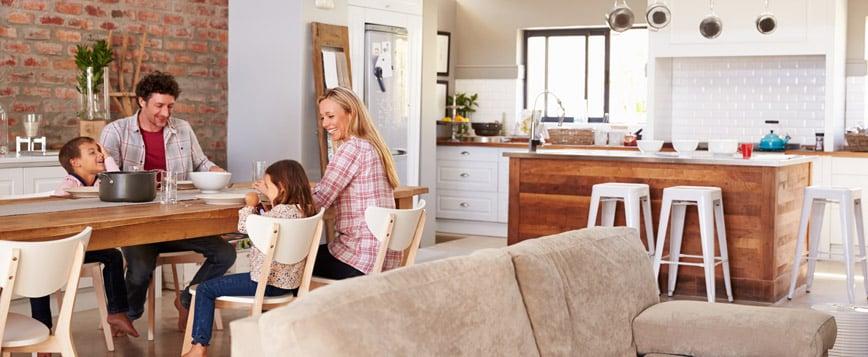 Perhe ruokailemassa uudessa talossa